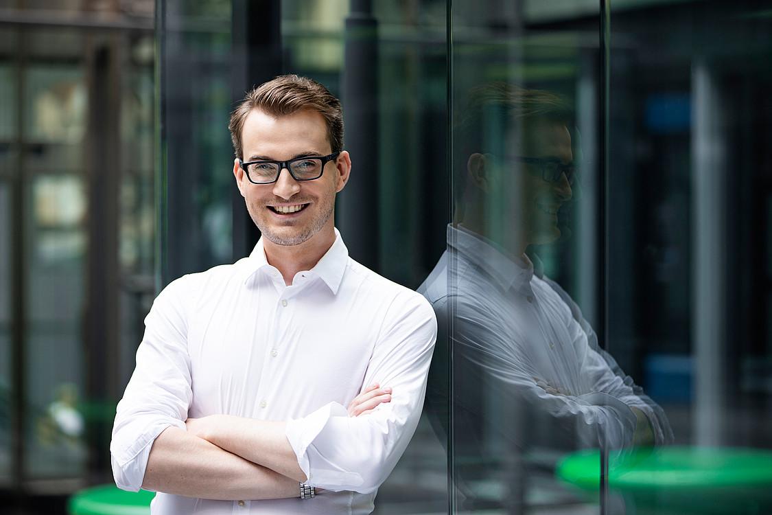 Karriere: Finanzberater lehnt an Glasscheibe