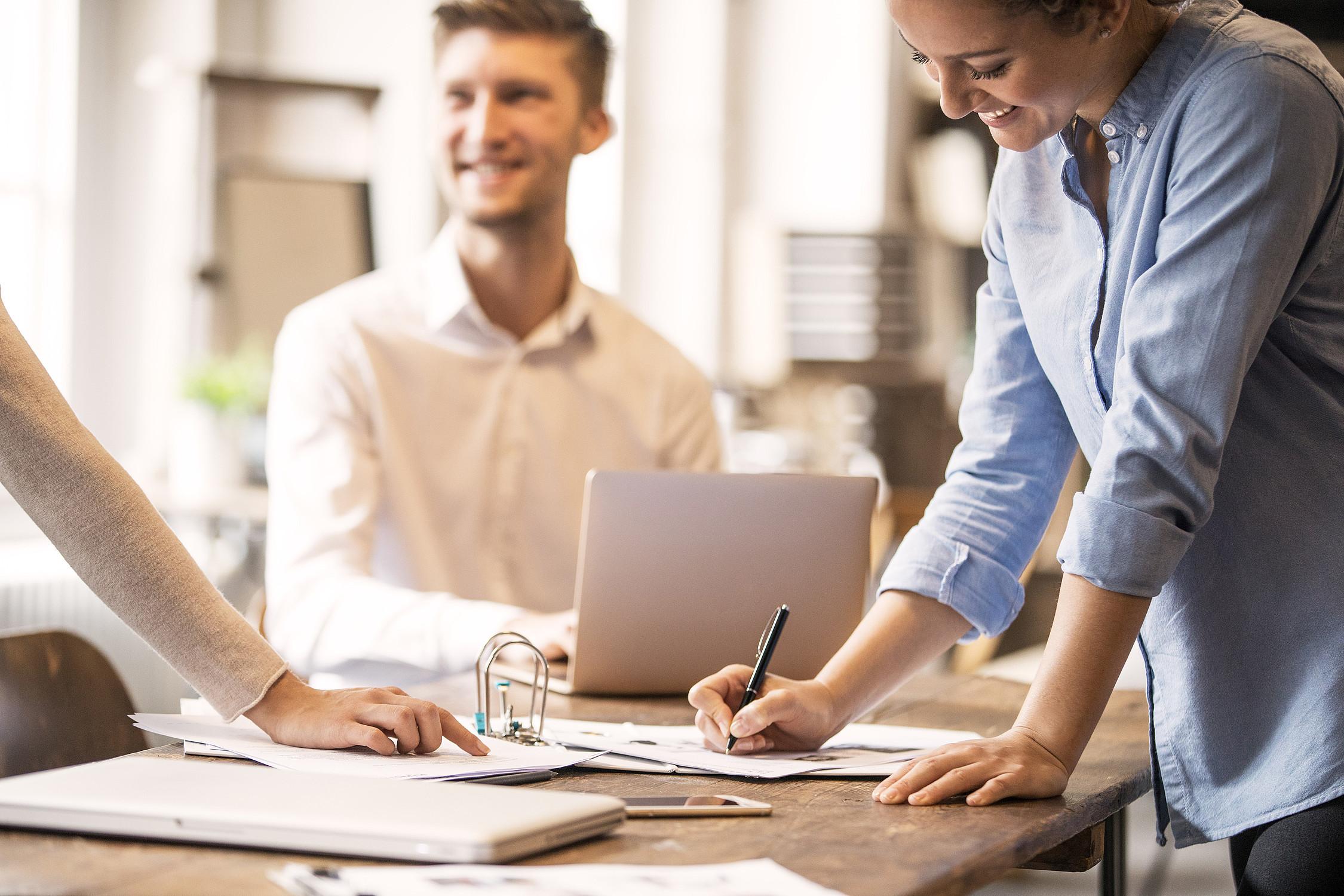 Frau macht Notizen während Finanzgespräch mit Kollegen