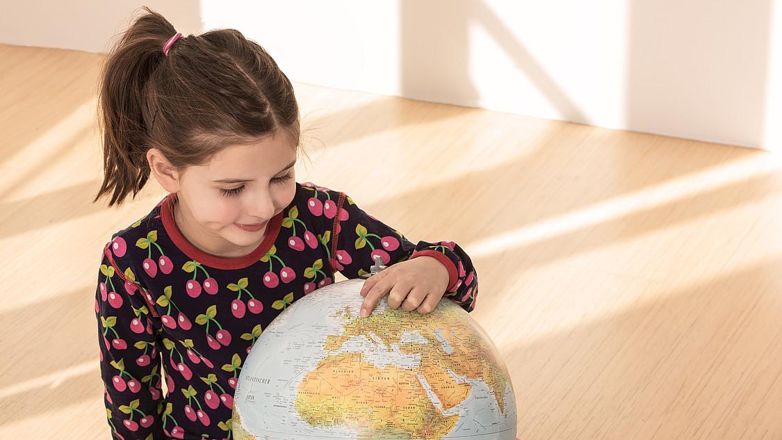 Europaweiter Finanzdienstleister: Mädchen betrachtet Globus